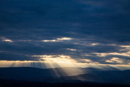 lining: break sunbeams the clouds over a mountain landscape