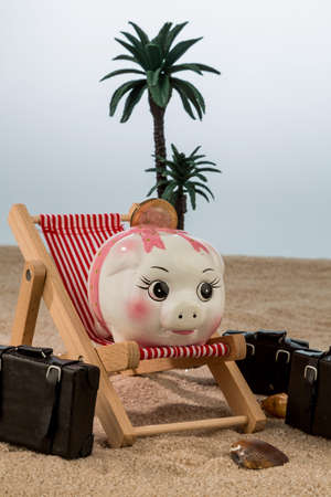 fare: a piggy bank is in a deckchair. symbolic photo for travel and low cost holiday Stock Photo