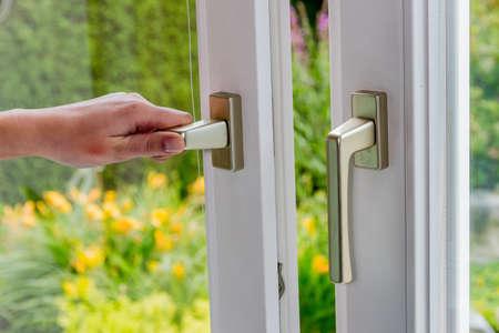 klima: eine Frau öffnet ein Fenster, um die Wohnung zu lüften. Frischluft in den Raum Lizenzfreie Bilder