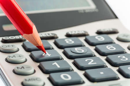 inventario: una pluma roja est� en una calculadora. ahorrar en costos, gastos y presupuesto para la mala econom�a