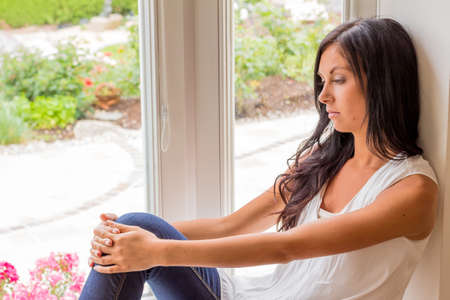 psychologically: a young woman sitting at the window and relax Stock Photo