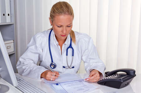 a young woman doctor with stethoscope in her doctors office. Stock Photo