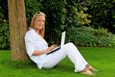 relaxen: a young woman sitting with a laptop computer in the garden and surf the internet. wi-fi in the park. Stock Photo