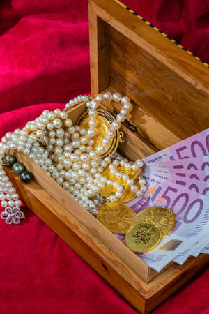 assessment system: gold in coins and bars with decorations on red velvet. symbolic photo for wealth, luxury, wealth tax.