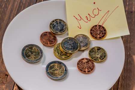 tax tips: a plate of coins for tips or fee for toilets. in french Stock Photo