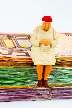 generational: figure of an old woman sitting on a stack of bills, symbol photo for pension and retirement