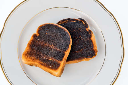burnt toast: toast was burned during toasting. burnt toast at breakfast. Stock Photo