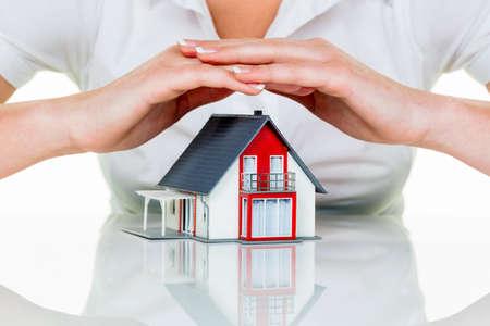 incendio casa: una mujer protege su casa y el hogar. un buen seguro y de buena reputación calma financiación.