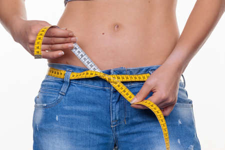 thinness: a young woman with a tape measure prior to the next diet. dieting and fasting Stock Photo