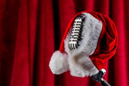 een oude retro microfoon met santa hoed tegen een rode fluwelen achtergrond.