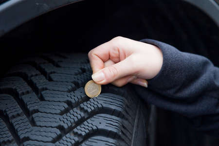 winter tire: a young woman measures the tread depth of your car tire. the correct depth in the tread of a tire can prevent accidents. Stock Photo