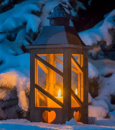 candela: una lanterna illumina la neve a Natale. luce romantica su una sera d'inverno. pace e tranquillità