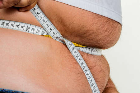 constrict: man with overweight. symbolic photo for beer belly, unsuccessful dieting and eating the wrong foods. Stock Photo