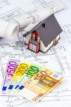 modell: a blueprint of an architect with euro money. symbolic photo for financing and planning of a new house. Stock Photo