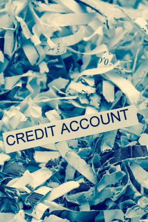 creditworthiness: papierschnitzel tagged with credit account, symbolfoto for data destruction, finance and credit Stock Photo