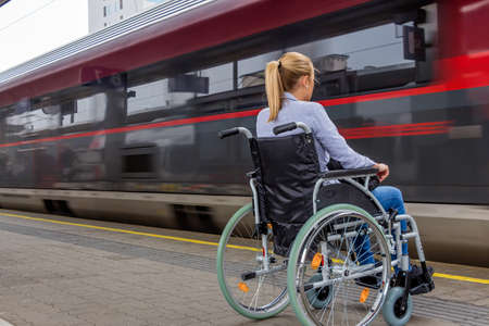 a young woman sitting in a wheelchair at a train station Stok Fotoğraf