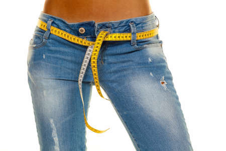 a young, slim woman in jeans with tape measure after a successful diet Standard-Bild