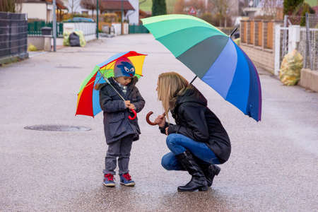 time deficit: mother and child with umbrella, a symbol of solidarity, assistance, bailout, bailout,