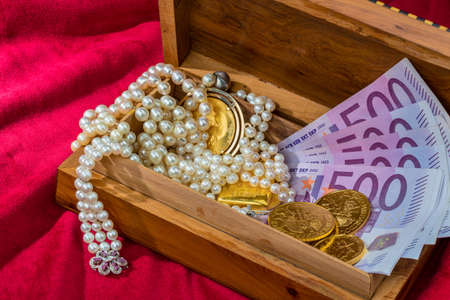 monetary devaluation: gold in coins and bars with decorations on red velvet. photo icon for wealth, luxury, wealth tax. Stock Photo