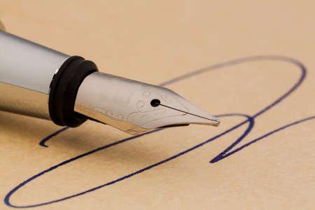 testament schreiben: eine Unterschrift und einen F�llfederhalter auf gelbem Papier. Symbolfoto f�r Vertrag, Testament und grafologie