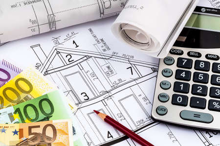 single familiy: a blueprint of an architect with a calculator and euro money. symbolic photo for financing and planning of a new house.