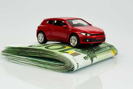 cost: a car standing on euro bills. costs for the purchase of automobiles, gasoline, insurance and other car costs
