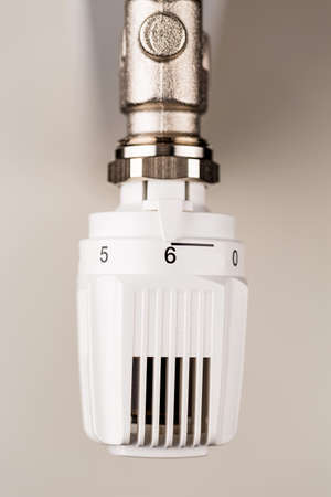 energy costs: the thermostat of a radiator is on full blast. high room temperature cause high energy costs