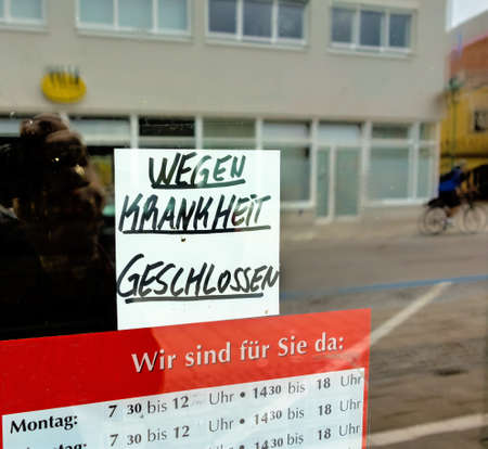 self operation: sign on the front door to a shop: closed due to illness Stock Photo