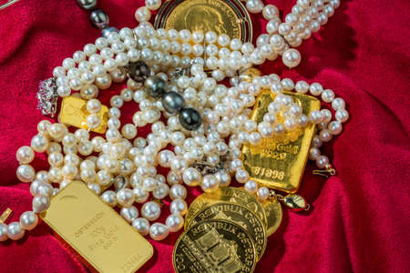 gold bars: gold in coins and bars with decorations on red velvet. photo icon for wealth, luxury, wealth tax. Stock Photo
