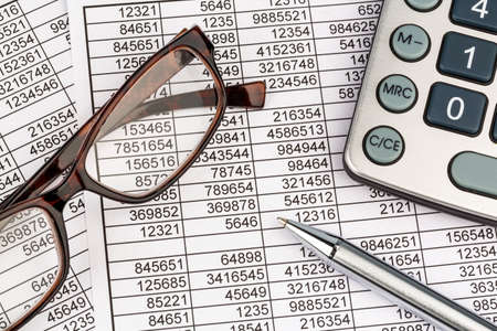 a calculator is located on the numbers a balance us statistics. photo icon for sales, profit and cost.