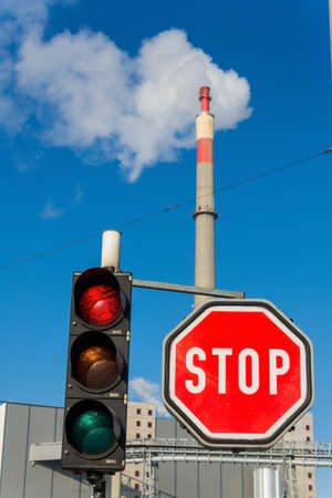 particulate: chimney of an industrial company and stop board. symbolic photo for environmental protection and ozone.
