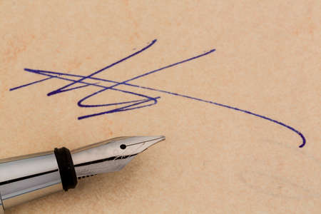 notieren: an agreement or document shall be signed by hand with a fountain pen. Stock Photo