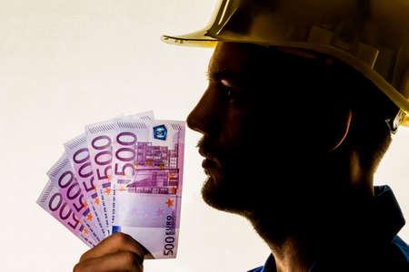 apprenticeships: a worker in a business enterprise (craftsmen) with money bills in his hand
