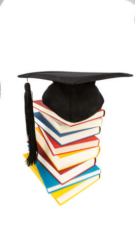 stacks: a mortar board on a pile of books, symbolic photograph of education and competence