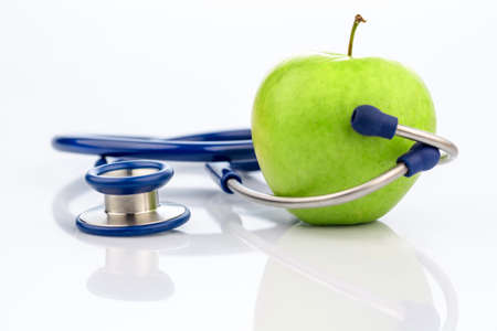 stethoscope: an apple and a stethoscope with a doctor. symbolic photo for healthy and vitamin-rich diet. Stock Photo