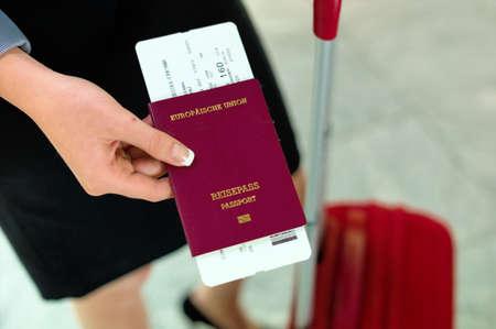 vrouw met paspoort en vliegtickets op een luchthaven te wachten op haar vertrek op vakantie.