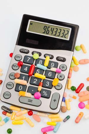 simbolo medicina: tabletas se encuentran en una calculadora. foto símbolo de los costos de la medicina y la industria farmacéutica