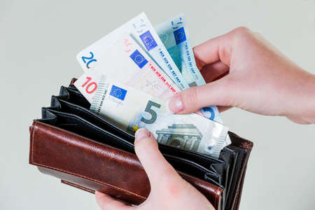seizure: in a purse there are several euro banknotes. money is running out through the new poverty.