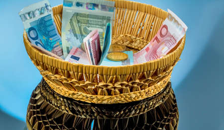 tax tips: a basket with money for donations and gratuities Stock Photo