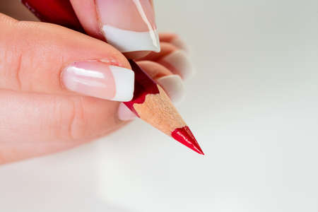 deletion: a hand holding a red pen. symbolic photo for savings and budegt cuts.