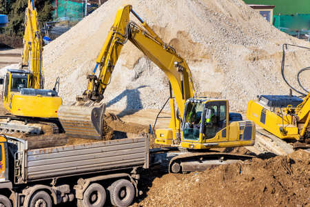 construction site: excavator on a construction site. excavator bucket with soil, earthworks. Stock Photo