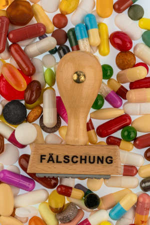 counterfeiting: stamp on colorful tablets symbolfoto drug counterfeiting and piracy