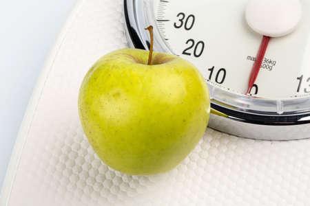 en una escala personal es una manzana. icono de la foto para la pérdida de peso y dieta saludable, rica en vitaminas. Foto de archivo