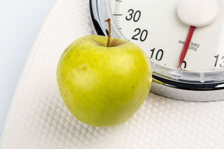 low scale: on a personal scale is an apple. photo icon for weight loss and healthy, vitamin-rich diet.