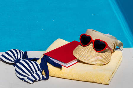 relaxen: utensils for a nice relaxing vacation day lying next to a swimming pool. recreation on vacation.