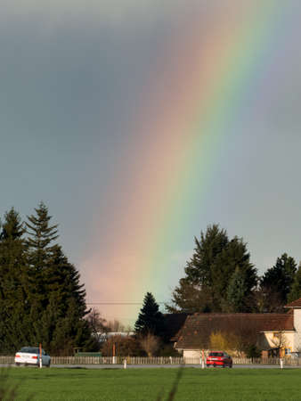 rain weather: after bad weather and rain enjoys a rainbow. Stock Photo