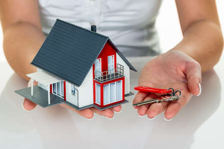 immobilien: an agent for property with a house and a key. successful leasing and property sales by real estate brokers. Stock Photo