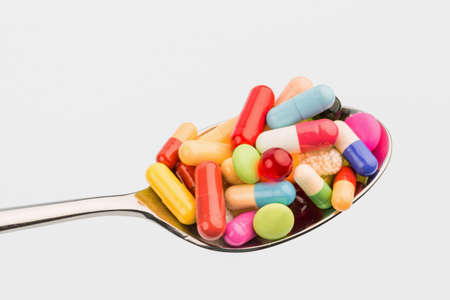 many colorful pills on a spoon. photo icon for tablets addiction and misuse of drugs.