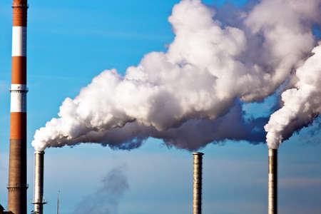 staub: die rauchende Schornsteine ??einer Fabrik gegen den blauen Himmel. für Kamine weißer Rauch steigt auf Lizenzfreie Bilder