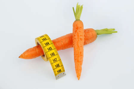thinness: carrots from organic farming with tape measure. fresh fruits and vegetables is always healthy. symbolic photo for healthy diet. Stock Photo